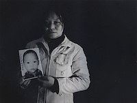 "Mrs Deng Yongmin, 31, holds a picture of her son Liu Lang, 5 years and 3 months, who was stolen in March 2003. The message reads ""My son, mummy hope you come back soon.""..PHOTO BY SINOPIX"