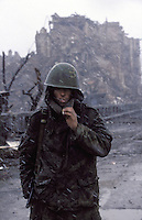 A Russian army conscript shelters against the cold and rain amid the destruction of the city centre...