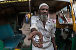 13 September, 2013, Ahmedabad, Gujarat INDIA :  A Muslim auto rickshaw driver shows his small change fares in a market in Juhapura, Ahmedabad.  Juhapura was a small suburb with a small population until the mid 80s, but after the communal riots of Gujarat from 1985 until 2002, a large number of the Muslims migrated to Juhapura from the Muslim and Hindu-dominated areas of Ahmedabad.  Chief Minister of Gujarat , Narendra Modi has been announced as the Prime Ministerial candidate for the opposition BJP party in the Indian general elections slated for 2014.   Mr.Modi has been a controversial figure since his involvement in the 2002 Gujarat riots where a train full of Hindu pilgrims was attacked by Muslims returning from a disputed temple site in Ayodhya.  In retaliation some estimate up to 2000 Muslims lost their lives in communal violence.   Mr. Modi is alleged to have condoned the violence despite being cleared of any allegations by a Special Investigation Team (SIT) appointed by the Supreme Court of India. Picture by Graham Crouch/New York Times