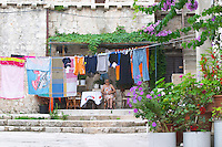 An old woman sitting in a court yard with clothes lines with colourful washing hanging to dry, surrounded by flowers Dubrovnik, old city. Dalmatian Coast, Croatia, Europe.
