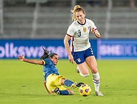 ORLANDO, FL - JANUARY 22: Samantha Mewis #3 of the USWNT steps through the tackle of Ana Huertas #5 of Colombia during a game between Colombia and USWNT at Exploria stadium on January 22, 2021 in Orlando, Florida.