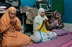 INDIA (West Bengal - Calcutta)July 2007,Shakila Babe(left) and Sanno Babe (right) offering Namaz along with their sister at their two roomed apartment in Iqbalpur.  10 family members share this apartment.   Shakila and Shanno are twins from a poor muslim family of Iqbalpur, Kolkata. . Inspite of their late father's unwillingness to send his daughters to take up  boxing her mother Banno Begum inspired them to take up boxing at the age of 3. Their father was more concerned about the social stigma they have in their community regarding women coming into sports or doing anything which may show disrespect to the religious emotions of his community. Shakila now has been recognised as one of the best young woman boxers of the country after she won the  international championship at Turkey in the junior category. Shanno is also been called for the National camp this year. Presently Shakila and shanno has become the role model in the Iqbalpur area  and parents from muslim community of Iqbalpur have started showing interst in boxing. Iqbalpur is a poor muslim dominated area mostly covered with shanty town with all odds which comes along with poverty and lack of education. - Arindam Mukherjee