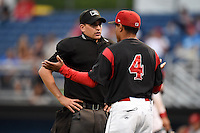 Umpire Anthony Perez explains a call to Angel Espada (4) during a game between the Brooklyn Cyclones and Batavia Muckdogs on August 11, 2014 at Dwyer Stadium in Batavia, New York.  Batavia defeated Brooklyn 4-3.  (Mike Janes/Four Seam Images)