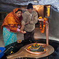 India, Dehradun.  Worshipers Placing a Candle in Homage to Sheshnag, the Divine Five-headed Serpent in Hindu Mythology, at Tapkeshwar Hindu Temple.