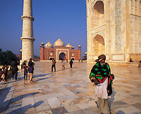 Vistors stroll the upper tiled marble walkway around the Taj Mahal, with the mosque of the Taj in the middle-distance under a blue sky; Agra, Indi