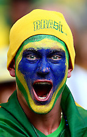 A Brazil fan with painted face cheers his side on
