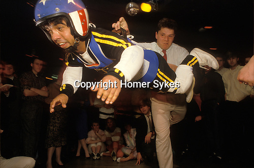 Croydon, Surrey. 1980's <br /> South Londoner Lenny Fowler, better known as Lenny the Giant, had a successful and varied career in the showbiz. He was the missile in the sport of dwarf throwing, seen here in Croydon nightclub being tossed through the air by clubbers. He claimed politicians and do-gooders had blighted his career.