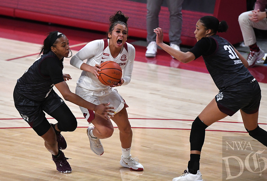 Arkansas' Chelsea Dungee makes a move to the basket between Texas A&M's Aaliyah Wilson (left) and N'dea Jones Sunday Jan. 10, 2021 at Bud Walton Arena in Fayetteville. Arkansas lost 74-73. Visit nwaonline.com/210111Daily/ and nwadg.com/photos. (NWA Democrat-Gazette/J.T. Wampler)