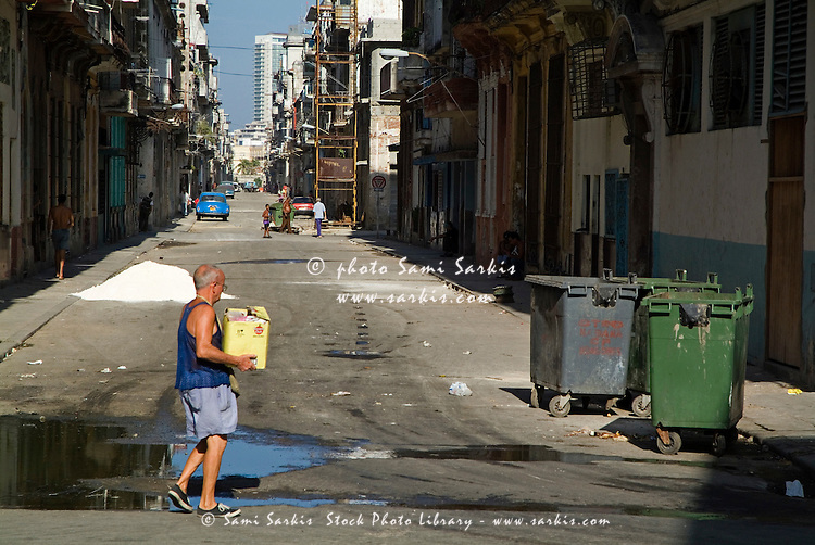 Man walking across a street to dump his rubbish in garbage containers, Havana streets, Cuba.