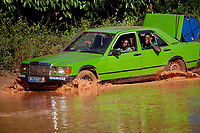 A group of men attempt to drive a Mercedes Benz car through a river.