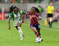 AUSTIN, TX - JUNE 16: Crystal Dunn #19 of the United States brings the ball up the field with Michelle Alozie #22 of Nigeria defending during a game between Nigeria and USWNT at Q2 Stadium on June 16, 2021 in Austin, Texas.