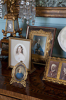 Detail of a collection of small Victorian family portraits on display on a chest of drawers in the library