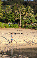 A boy standing on the beach near a tide pool on the North Shore, O'ahu.