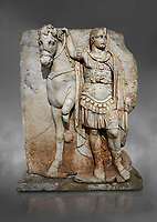Roman Sebasteion relief sculpture of  an Imperial prince as Diokouros, Aphrodisias Museum, Aphrodisias, Turkey.  Against a grey background.<br /> <br /> An imperial youth wearing a military cloak and cuirass of a commander holds the reins of hios horse. This panel is next to a Claudius panel so is probably of Britanicus or Nero the emperors son and intended successor