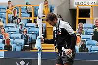 A member of ground staff cleans the corner flag with disinfectant prior to kick-off during Millwall vs Middlesbrough, Sky Bet EFL Championship Football at The Den on 8th July 2020