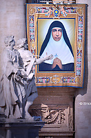 tapestry portraying Maria Teresa Chiramel Mankidiyan  hangs from the facade of St. Peter's Basilica, at the Vatican. Pope Francis during  Canonization Mass for English John Henry Newman, Italian Giuseppina Vannini, Indian Maria Teresa Chiramel Mankidiyan, Brazilian Dulce Lopes Pontes, and Swiss Margarita Bays on October 13, 2019 In Saint Peter's square at the Vatican.