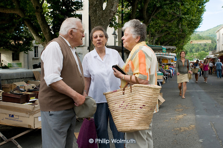 Three elderly residents stop to talk in the street on market day in a small town in southern France