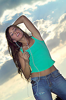 Beautifull woman listening to music through headphones outdoors as she dances