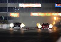 May 18, 2012; Topeka, KS, USA: NHRA funny car driver Courtney Force (left) races alongside Johnny Gray during qualifying for the Summer Nationals at Heartland Park Topeka. Mandatory Credit: Mark J. Rebilas-