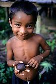 Brazil. Tumucumaque National Park; Waiapi Indian boy holding a buriti palm nut.