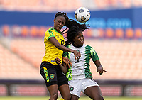 HOUSTON, TX - JUNE 10: Sashana Campbell #12 goes up for a header with Toni Payne #9 of Nigeria during a game between Nigeria and Jamaica at BBVA Stadium on June 10, 2021 in Houston, Texas.