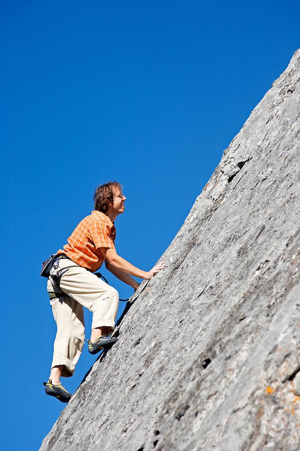 Male climber on rock face against blue sky, Banff, Banff National Park, Alberta, Canada