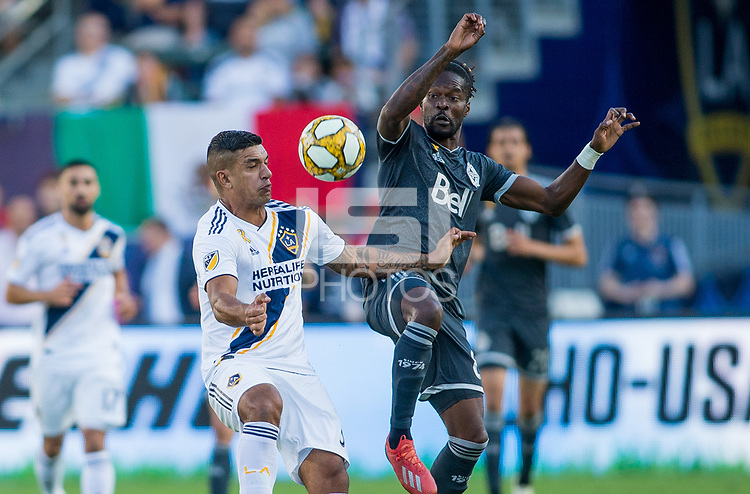 CARSON, CA - SEPTEMBER 29: Diego Polenta #3 of the Los Angeles Galaxy and Tosaint Ricketts #87 of the Vancouver Whitecaps battle for a ball during a game between Vancouver Whitecaps and Los Angeles Galaxy at Dignity Health Sports Park on September 29, 2019 in Carson, California.