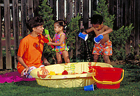 AFRICAN-AMERICAN MOTHER AND TODDLERS PLAYING WITH WATER. AFRICAN-AMERICAN FAMILY. OAKLAND CALIFORNIA.