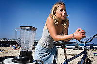"""Saturday, June 21 2009.  Pacific Beach, San Diego, CA, USA:  Anna Cummins of the environmental group Algalita Marine Research Foundation (AMRF) gets ready to make breakfast with her bicycle-powered blender on the beach in PB one day after completing a six-week journey from Vancouver to TJ with her husband Dr Marcus Eriksen, to raise awareness about marine debris.   The couple spoke at 40 different events along the way and presented 5 mayors with samples of the """"plastic soup"""" that they collected form a remote part of the Pacific Ocean known as the North Pacific Gyre.  The confluence of currents in that area of the Pacific has created a high concentration of marine debris - particularly plastics - that is clogging the area, endangering marine life and entering our food chain."""