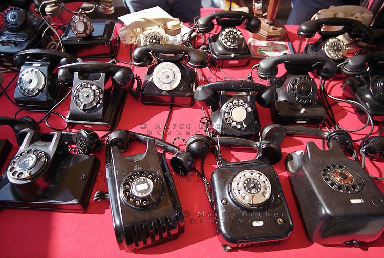 Milano, vecchi telefoni su una bancarella del mercatino dell'antiquariato al Naviglio Grande --- Milan, old telephones on a stall at the antiques market at the Naviglio Grande channel