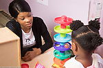 Education Preschool Phase-in First Days of School toddler 2s female teacher talking to girl playing with ball tower toy