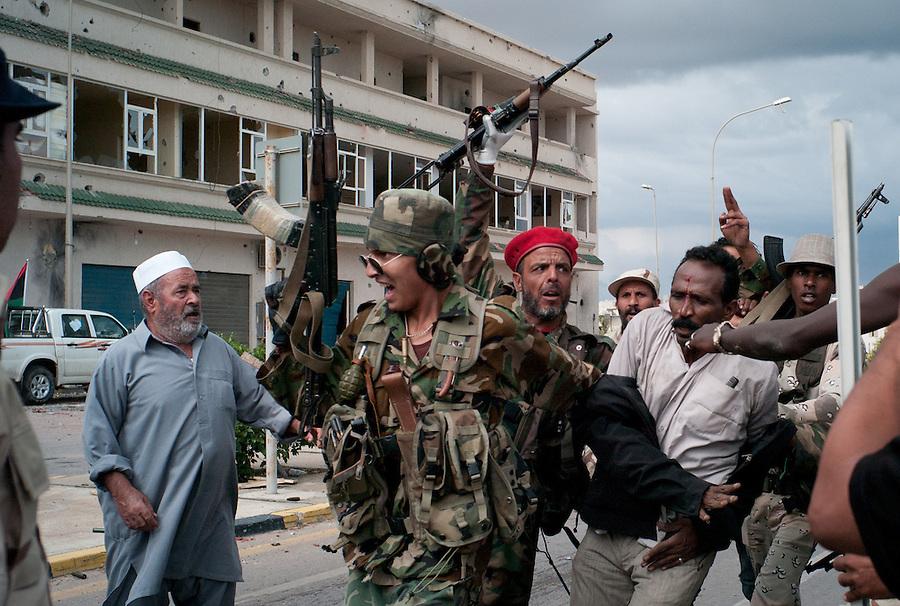 Anti-Gaddafi fighters with a suspected Gaddafi loyalist captured in Sirte, Libya.