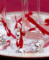 Small tags with Christmas messages are attached to champagne flutes with red ribbons