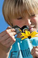 Kind, Junge betrachtet eine Blume, Blüte mit der Lupe, Klapplupe, Klapp-Lupe