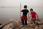 My older son, then five, helps his younger brother, then two, out to the edge of Lake Springfield in Illinois.
