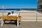 Couple sitting on bench overlooking beach on the new Asbury Park boardwalk, New Jersey