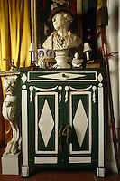 A feathered hat rests jauntily on the head of this bust  on a green and white painted cabinet