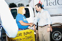 Texas senator and Republican presidential candidate Ted Cruz greets Shalom International president Bob Kunst, of Miami, Florida, who was holding an anti-Hillary Clinton sign while wearing a halloween mask bearing her likeness outside the kick-off event at his New Hampshire campaign headquarters in Manchester, New Hampshire.