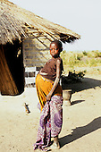 Lusaka, Zambia. Very pregnant young African woman in ragged clothes outside her poor house on the outskirts of the city.