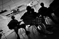 Members of the Mara Salvatrucha gang (MS-13) play guitar during the resocialization classes in the prison of Tonacatepeque, El Salvador, 18 May 2011. During the last two decades, Central America has become the deadliest region in the world that is not at war. According to the UN statistics, more people per capita were killed in El Salvador than in Iraq, in recent years. Due to the criminal activities of Mara Salvatrucha (MS-13) and 18th Street Gang (M-18), the two major street gangs in El Salvador, the country has fallen into the spiral of fear, violence and death. Thousands of Mara gang members, both on the streets or in the overcrowded prisons, organize and run extortions, distribution of drugs and kidnappings. Tattooed armed young men, mainly from the poorest neighborhoods, fight unmerciful turf battles with their coevals from the rival gang, balancing between life and death every day. Twenty years after the devastating civil war, a social war has paralyzed the nation of El Salvador.