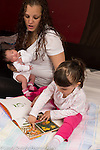 Two year old toddler girl with newborn baby sister and mother, age 25, looking at book together, talking