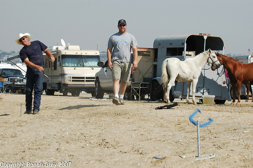 Kevin Rohr (L) of Poway and Mike Bates of Ramona were evacuated to Fiesta Island from their homes due to the San Diego wildfires, Tuesday, October 23, 2007.  They tried to pass the time calmly with a friendly game of horse shoes while waiting to be allowed back to their homes.