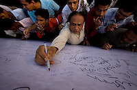 People write on a message board in front of the Taj Mahal Palace Hotel after multiple terrorist attacks were launched in Mumbai on 26/11/2008..