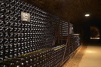 In the underground wine cellar: a pile of thousands of bottles of Chablis Les Preuses Grand Cru 1998 white Burgundy wine with the appellation written in white text on a black chalkboard chalk board on a gravelly pebbly soil, Maison Louis Jadot, Beaune Côte Cote d Or Bourgogne Burgundy Burgundian France French Europe European