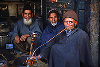 MUSLIM KASHMIRI MEN smoke a HUKKAH (hookah) in front of a small STORE - KASHMIR, INDIA.