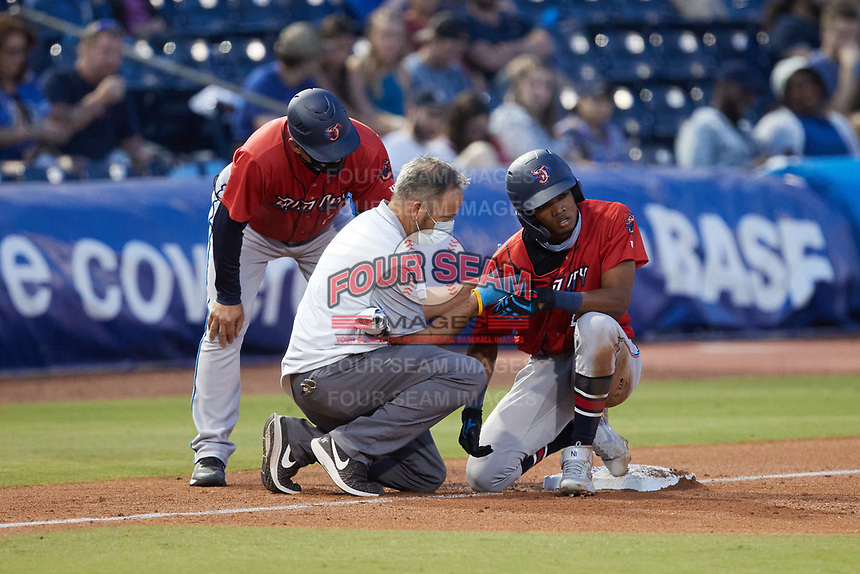 Jose Devers (27) of the Jacksonville Jumbo Shrimp is checked out by trainer Greg Harrel (center) and manager Al Pedrique (left) after getting hit in the right shoulder by a throw during the game against the Durham Bulls at Durham Bulls Athletic Park on May 15, 2021 in Durham, North Carolina. (Brian Westerholt/Four Seam Images)
