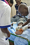 An ER technician fixing a mans toe in the ER of  Kibuye Hospital, Karongi District, Western Rwanda
