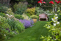 Grass lawn path with perennial border leading to garden bench at Digging Dog Nursery