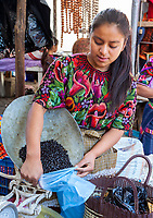 Chichicastenango, Guatemala.  Young Woman Putting Black Beans into a Bag for a Customer.