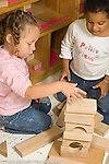 Preschool 3 year olds two girls building with blocks talking